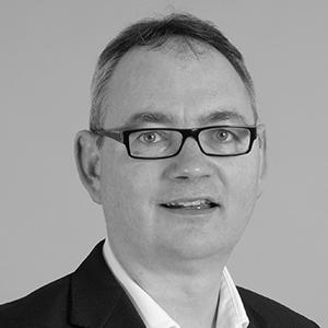 A black and white image of a man wearing glasses