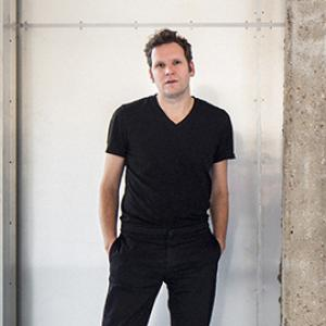 A person with black clothes posing with hands in pockets.