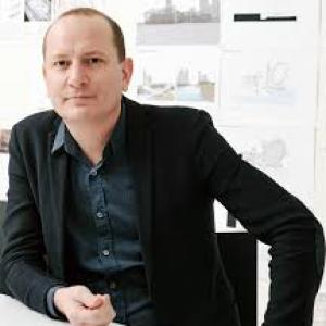 Man in black jacket sitting in front of architectural drawings.