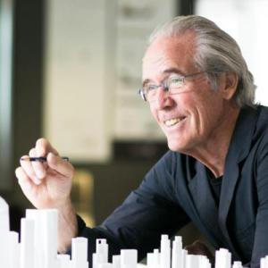 A man wearing glasses gestures over the model of a cityscape