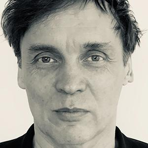 a dark haired man against a white background
