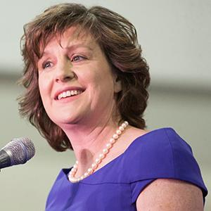 A woman with short brown hair wearing a pearl necklace and purple shirt speaks into a microphone.