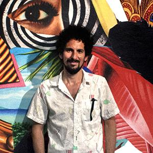 Man with dark hair, dark facial hair in front of large colorful mural with eye and stripes and leaves