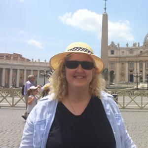 woman in a straw hat standing in front of a cathedral in Italy