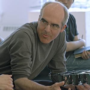 man with glasses and gray hair leaning on a table talking to someone out of the frame