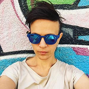 a woman wearing sunglasses against a colorfully painted wall