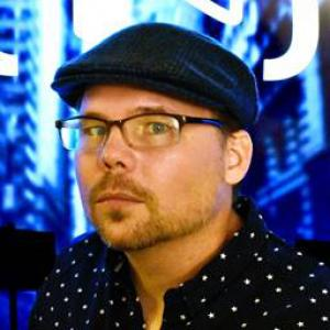 Man wearing glasses, a dark hat and polka dotted shirt against a bright blue hued background.
