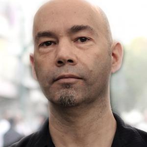A bald man wearing a black button up shirt.