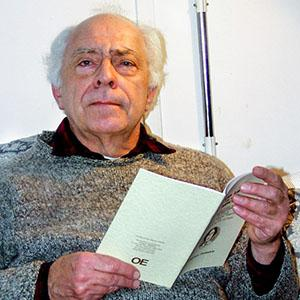 A man holding a book leaning against a white wall.