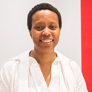headshot of an African American woman standing in front of a white wall with a red stripe