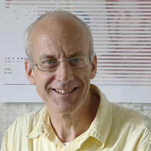 headshot of a man with glasses wearing a yellow shirt