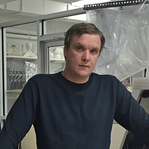 Man with short hair wearing a dark shirt in a lab setting