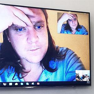 a man's face on a computer monitor, image repeated in the top right corner
