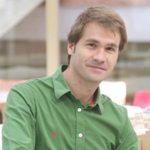 headshot of a man in a green button down shirt