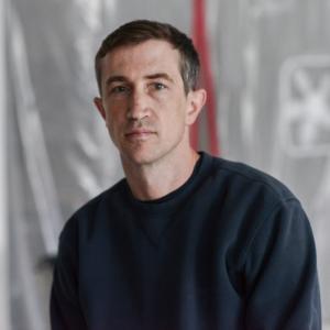 headshot of a man in a black shirt