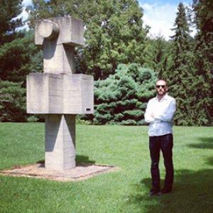 man standing beside a tall concrete sculpture