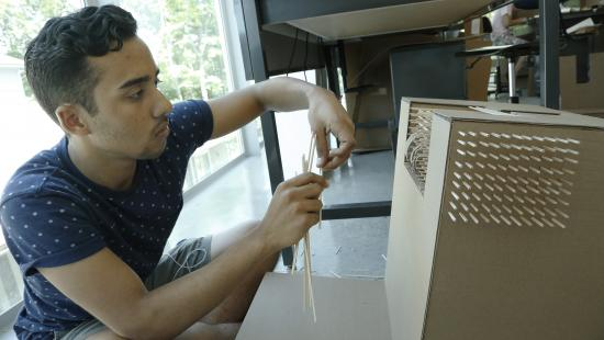 young man working on a cardboard model of a building