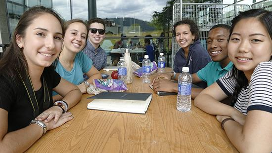 A group of students sitting around a wooden table with water bottles on it