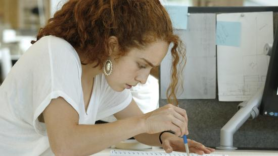 young woman with red hair and a white t-shirt leaned over a desk sketching