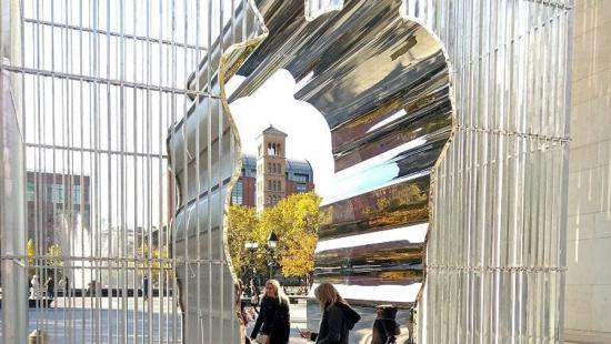 Chrome mirror-like artistic archway with people underneath.