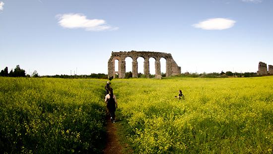 ruin of a Roman aqueduct set in a green field with blue sky and students walking towards it