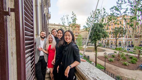 five students standing on a balcony overlooking a street
