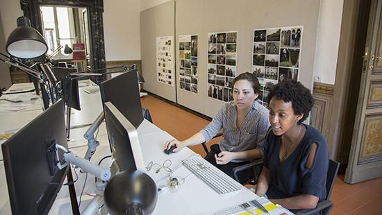 two students in the foreground looking at a computer screen with pinned projects on the background wall