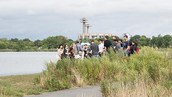 a group of people standing in the grass near water with the World's Fair grounds in the distance