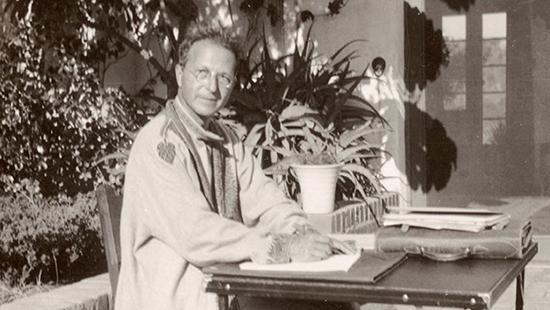 black and white image of a man in an overcoat sitting at a desk outside