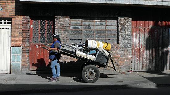 A person pulls a cart loaded with obsolete technology in front of a brick building