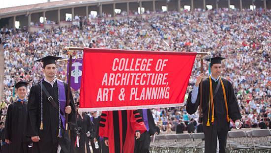 students in cap and gown holding a red banner that says College of Architecture, Art, and Planning