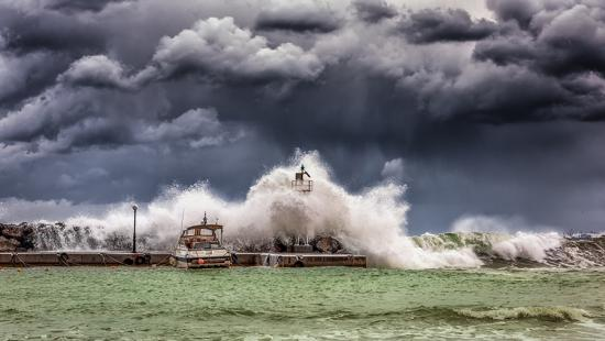 large waves crashing on a pier and boat