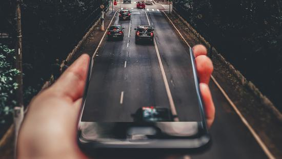 person's hand holding a smart phone with the top edge morphing into lanes of traffic