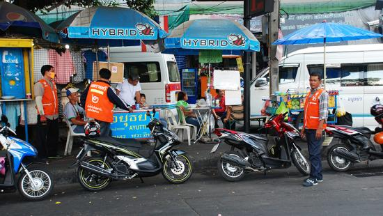 Motorcycle taxis parked on the side of a road with their drivers standing nearby