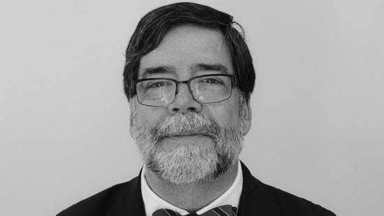 headshot of a man with a beard and glasses