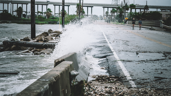 a wave crashing over a concrete road divider and onto the road