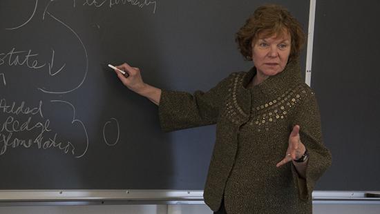 Susan Christopherson writing on a blackboard