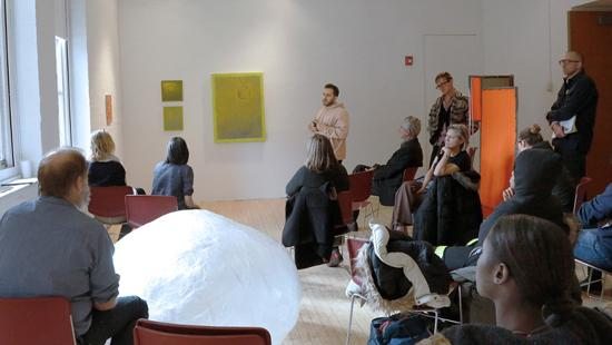 students and faculty gathered in a gallery to discuss work