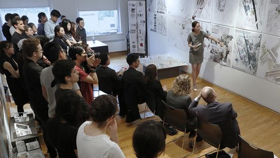 Female student presenting pinned plots of a project to a seated and standing audience