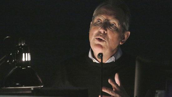 man with glasses speaking in a dark room with lamp on left.