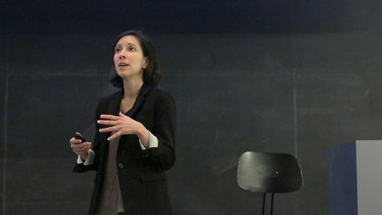 Woman gesturing with her hands, standing in front of a blackboard.