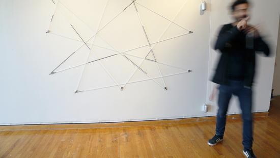 String and pulley sculpture on wall with blurred figure pointing on right.