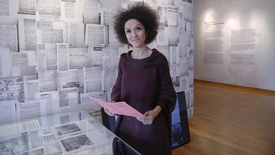 Woman standing next to a wall covered with printed papers.