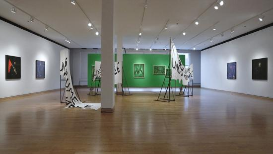 A view of an art gallery with portraits on white walls, steel and cloth sculpture, and green images on a green wall.