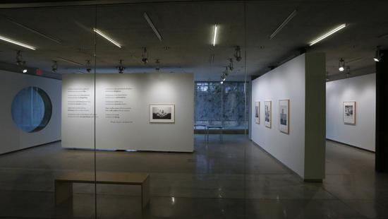 View of an art gallery with framed images and text on white walls.