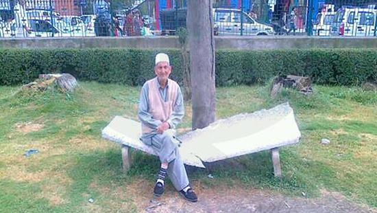 Grainy image of a man sitting on a broken bench in the park with traffic behind him.