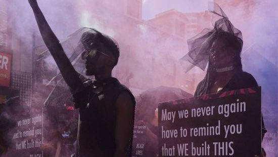 Two protesters wearing dark clothing, one with his fist raised in the air and a woman holding a protest sign with smoke in the air