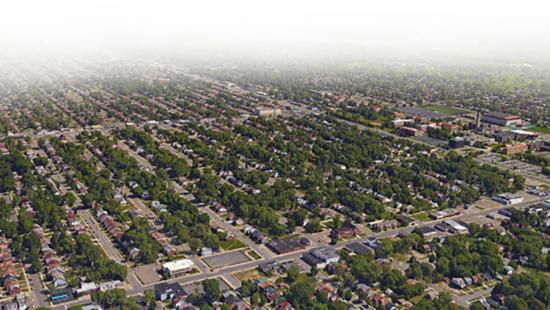 Arial view of an urban setting which consists of a series of tightly nit trees, houses, and streets.