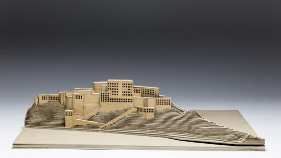 wooden model of a building set into some cliffs