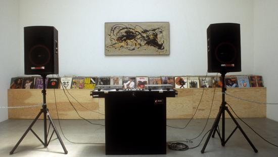 installation of two large speakers on stands, and a rectangular painting on a wall over a case of records